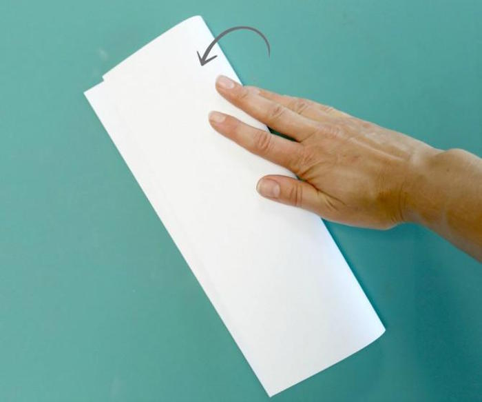 turquoise background paper airplane instructions white piece of paper folded in two step by step diy tutorial