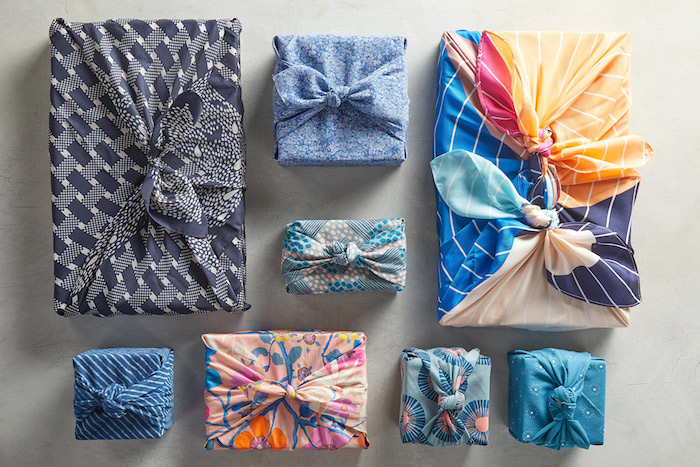 two big presents and six smaller ones wrapped in fabrics with different prints gift wrap ribbon placed on gray surface