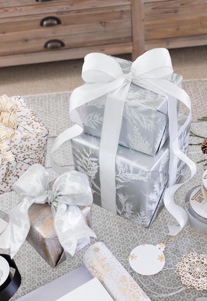 two boxes wrapped in silver wrapping paper how to wrap a present wrapped together with white ribbon