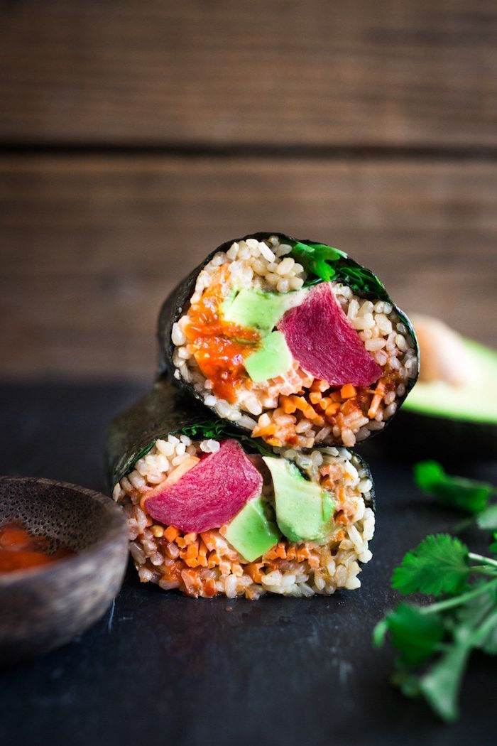 two sushi burritos with rice avocado parsley crab meat placed on black cutting board california roll recipe