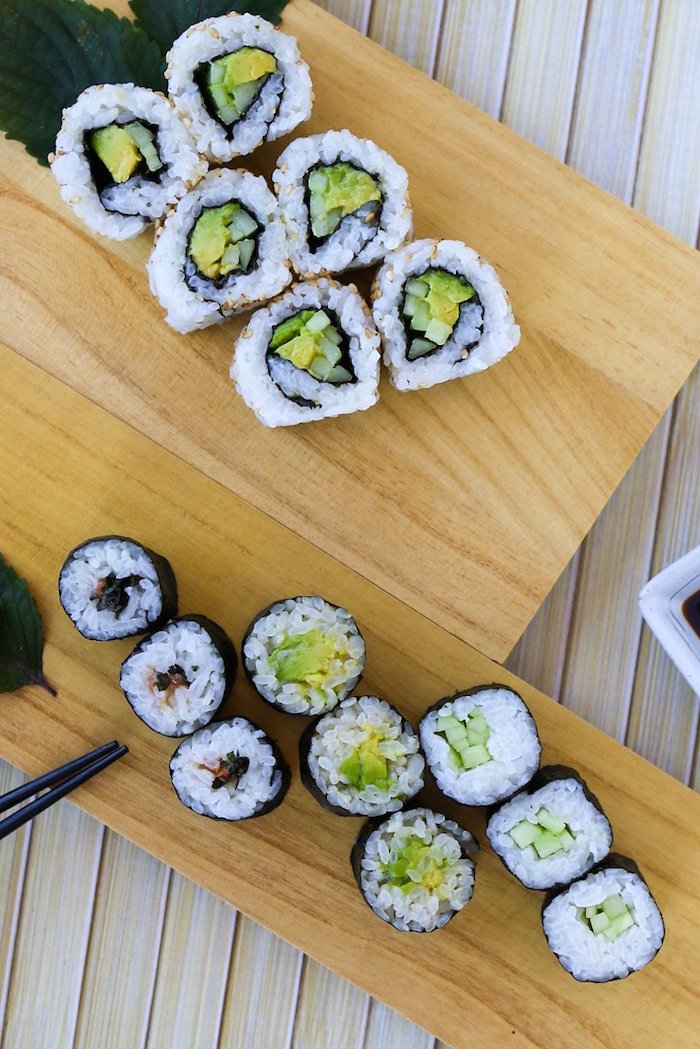 types of sushi rolls sushi with rice avocado arranged on wooden cutting boards black chopsticks on the side