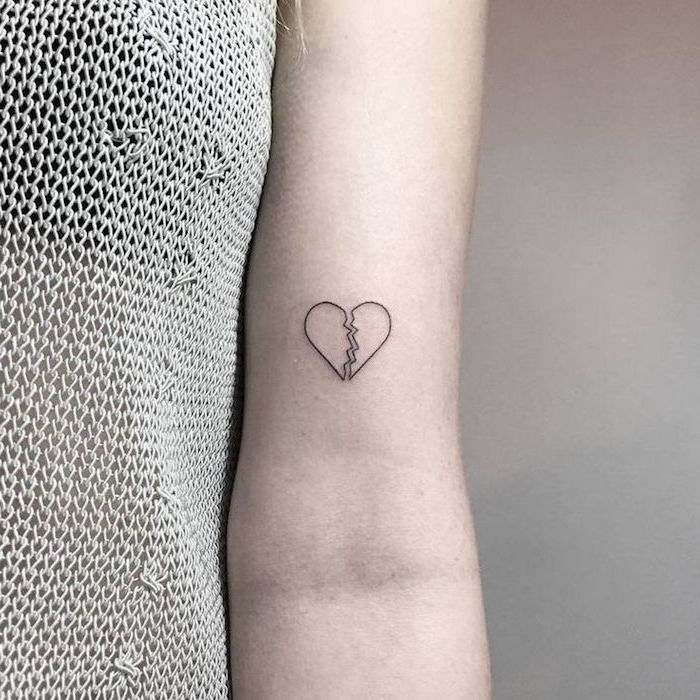 white background broken heart tattoo with black outlines not filled with ink inside the arm tattoo