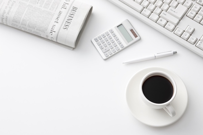 white desktop with newspaper white keyboard white calculator and pen and cup of coffee on it minimalist wallpaper