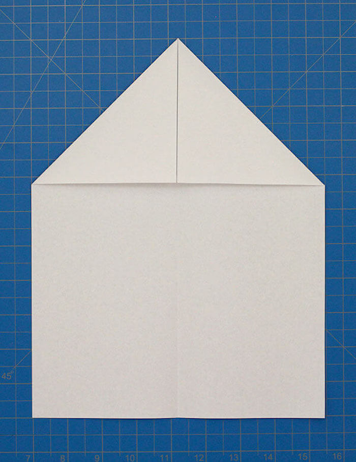 white piece of paper folded into a plane step by step paper airplane blue background diy tutorial