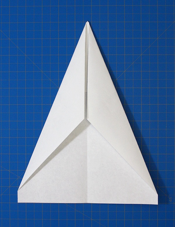 white piece of paper folded into a triangle on blue background step by step paper airplane