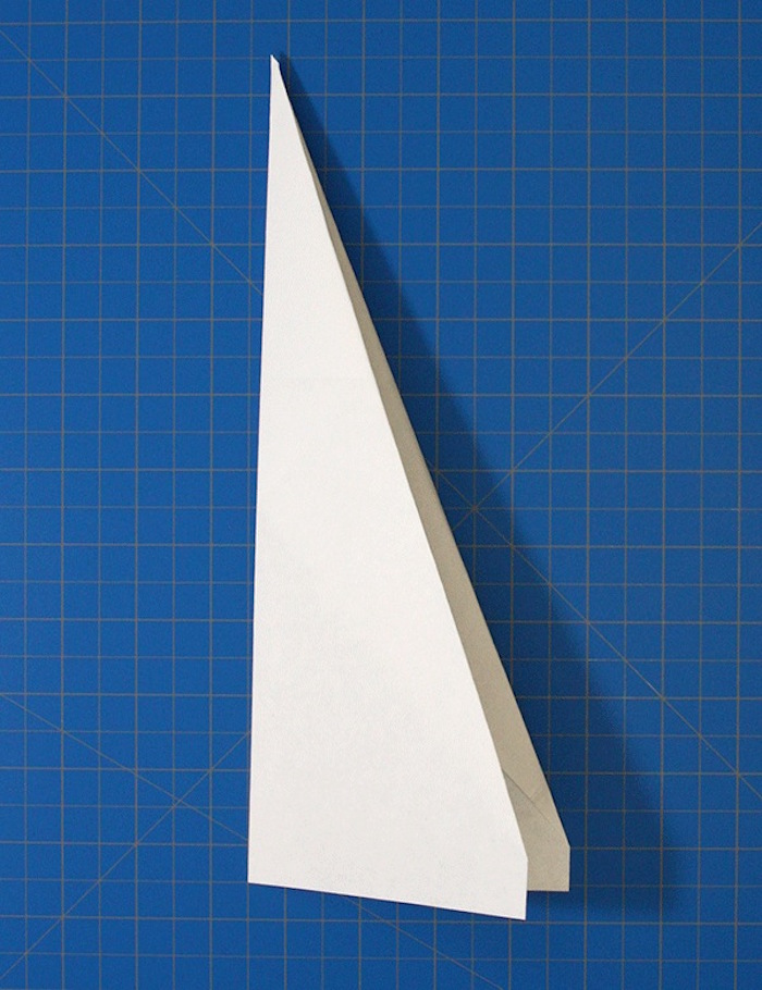 white piece of paper folded into plane how to make a paper airplane that flies far blue background