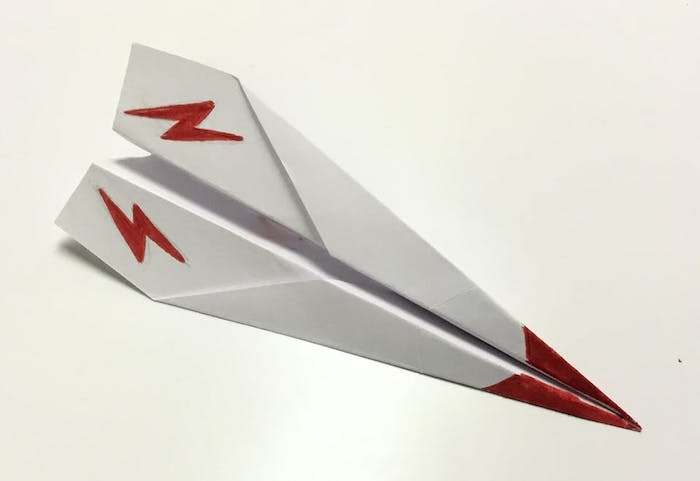 white piece of paper folded into plane simple paper airplane red flashes and red tip drawn on it placed on white background