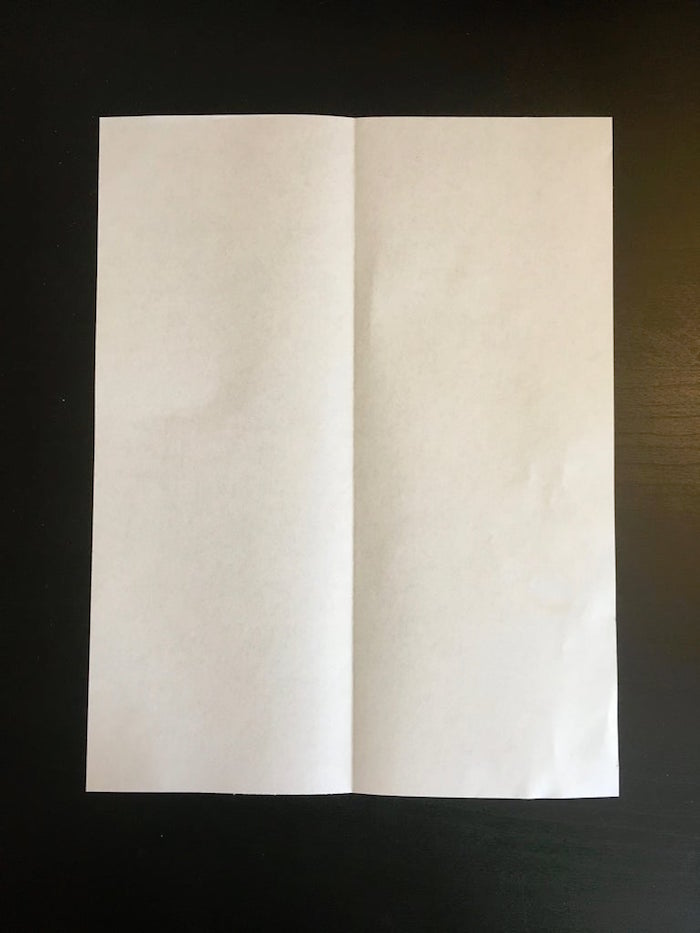 white piece of paper placed on black background folded in two and opened flat on the surface paper airplane folding