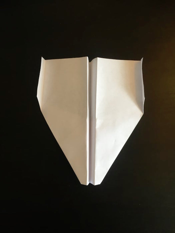 white piece of paper turned into a plane best paper airplane design photographed on black background