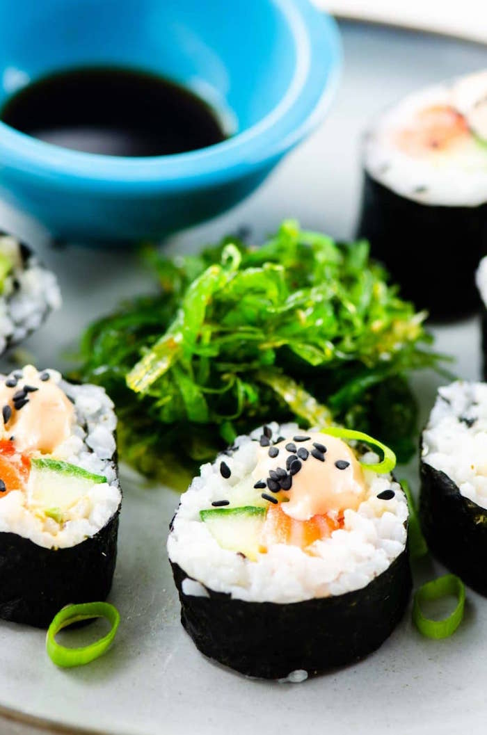 white plate shrimp tempura roll sushi with black sesame seeds arranged on it next to bowl of soy sauce
