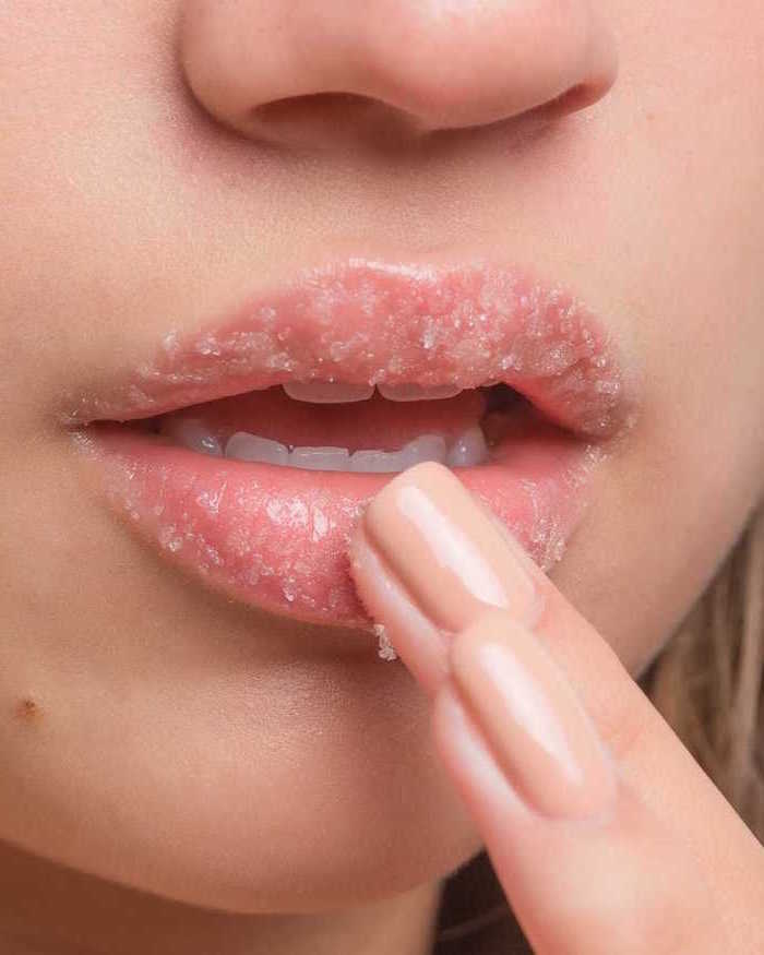 woman applying homemade lip scrub close up photo of lips woman with blonde hair