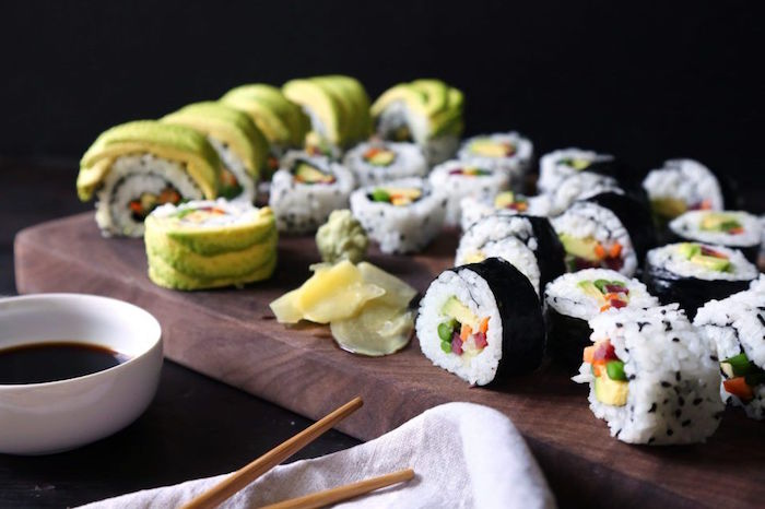 wooden cutting board how to make sushi at home vegetable sushi rolls arranged on it rolled in different ways