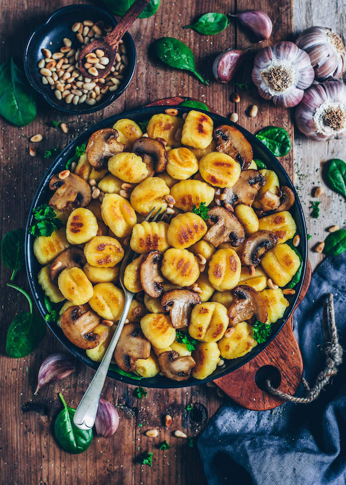 baked gnocchi with mushrooms pine nuts spinach what is gnocchi baked in black casserole placed on wooden surface