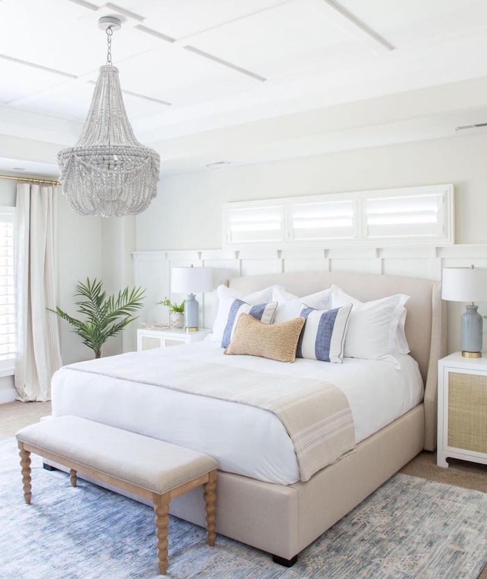 beach decor king size bed with beige bed frame throw pillows in blue and white glass chandelier above it