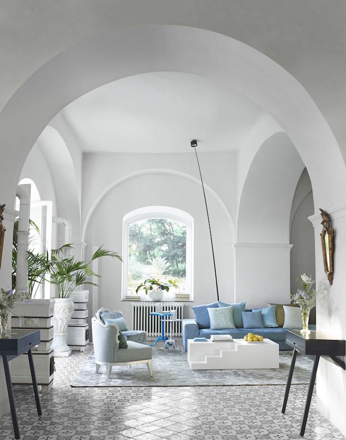 beach house decor open plan living room with cathedral ceiling blue sofa gram armchairs lots of blue throw pillows tiled floor