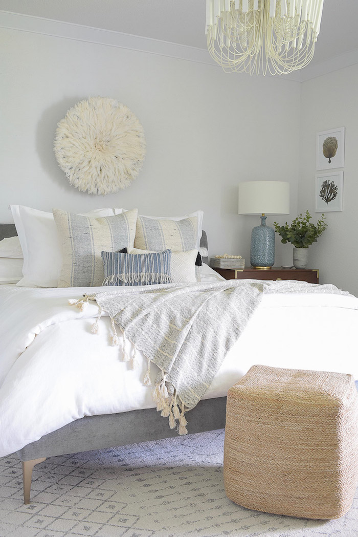 beach themed decor bed with gray bed frame throw pillows in gray and blue placed on white carpet white walls