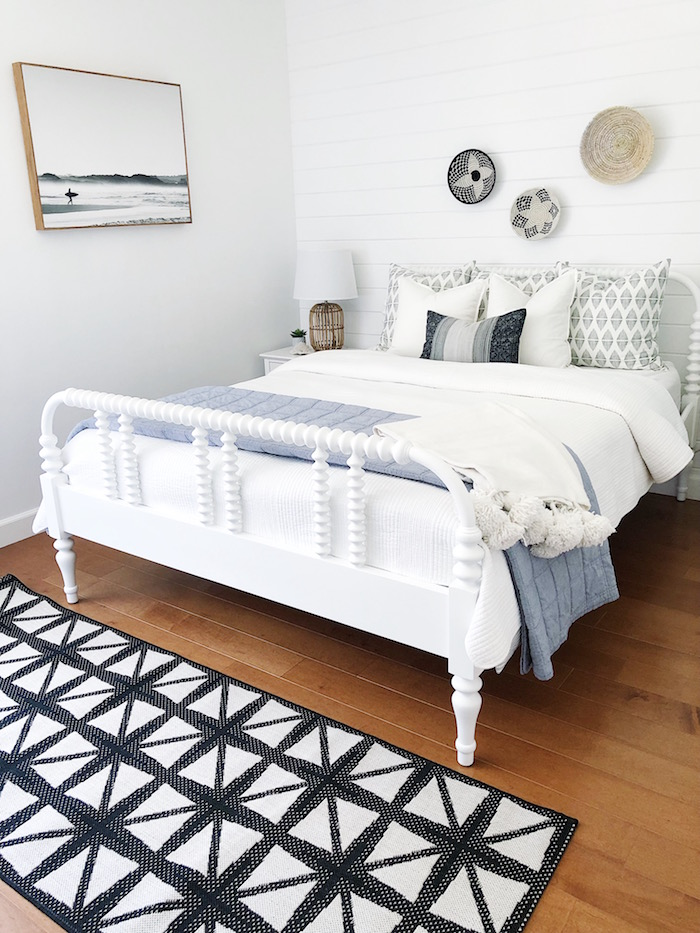 bedroom with wooden floor and white shiplap black and white carpet in front of bed with white bed frame coastal living room