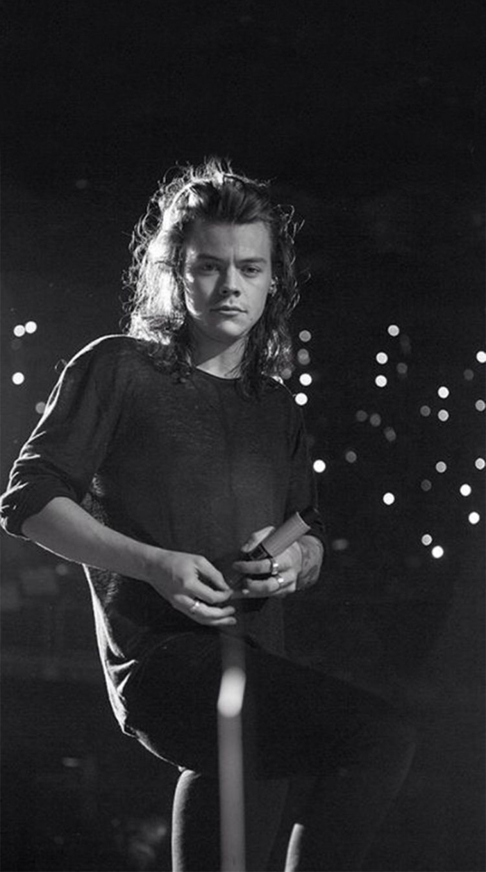 black and white photo of harry with long curly hair harry styles iphone wallpaper standing on stage