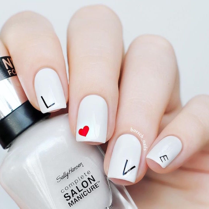 black letters spelling love on white nail polish with red heart on middle finger valentines day nails short square nails