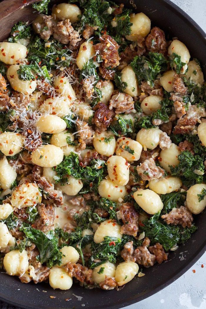 black pan easy gnocchi recipe with italian sausage kale garnished with grated parmesan cheese