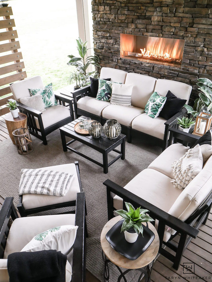 black wooden sofas and armchairs with white cushions green and white throw pillows beach themed decor stone fireplace