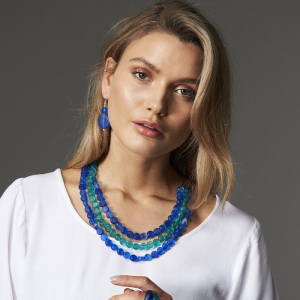 blonde woman wearing resin earrings necklaces and rings in blue and turquoise wearing white blouse