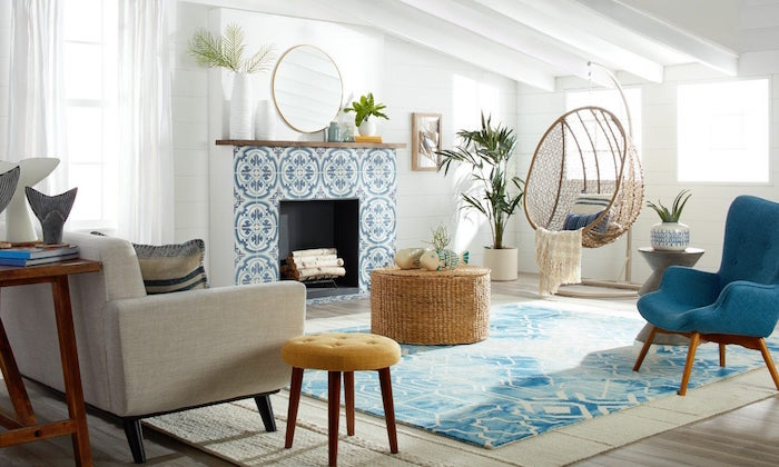 blue armchair and carpet in front of fireplace covered with blue and white tiles coastal living room with white shiplap walls