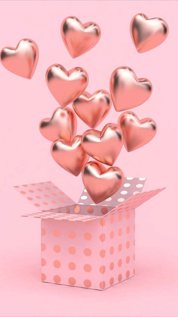 box wrapped in pink with golden dots on it filled with rose gold heart shaped balloons valentine's day origin pink background