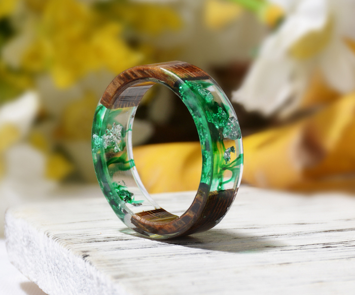 bracelet made of wood and resin resin jewelry molds clear with dried flowers inside in green and white placed on white wooden surface