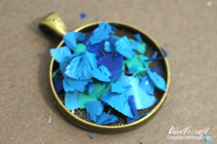 bronze vintage empty necklace pendant filled with blue and green crayon shavings epoxy jewelry step by step diy tutorial