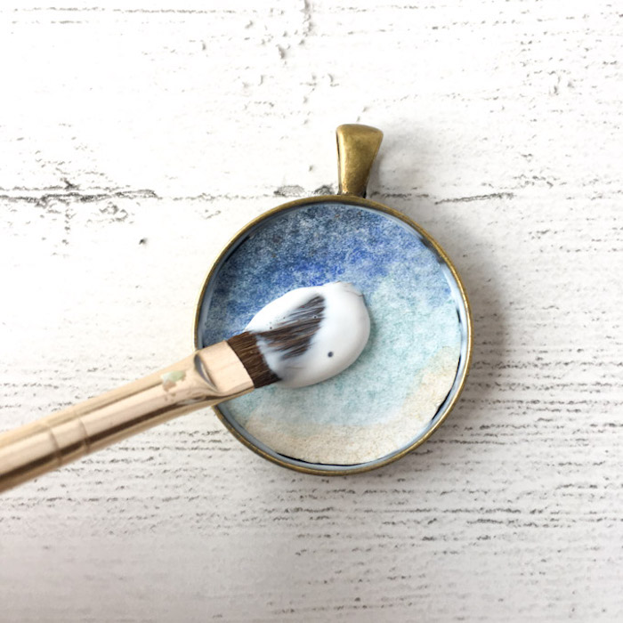 bronze vintage necklace pendant jewelry making for beginners blue watercolor paper placed on the bottom