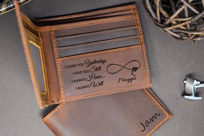 brown leather wallet with personalised message engraved inside valentines day gifts for boyfriend placed on gray surface