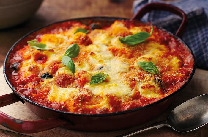 casserole with baked gnocchi with tomato sauce grated cheese on top gnocchi recipe garnished with fresh basil leaves