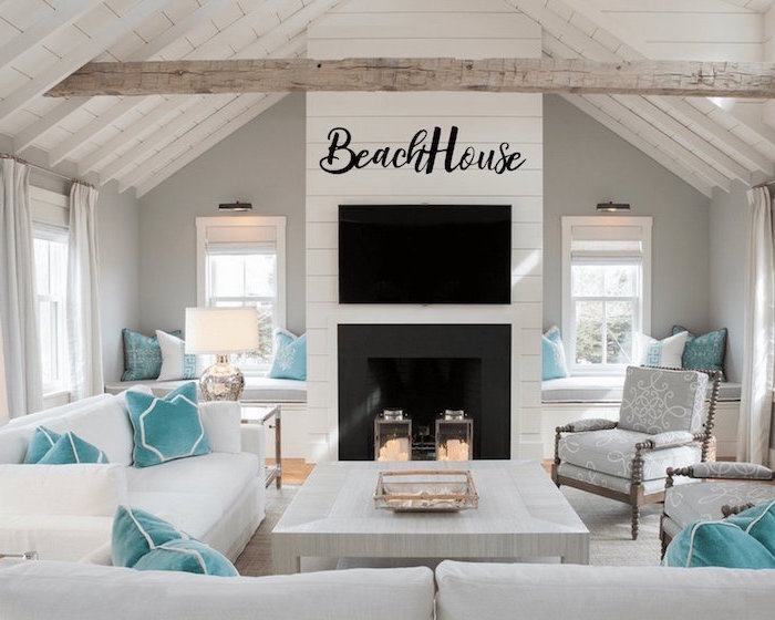 cathedral ceiling with exposed wood beams coastal decor white sofas gray armchairs with blue throw pillows in front of fireplace