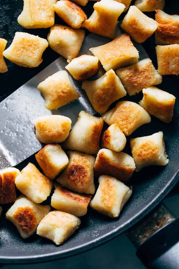cauliflower gnocchi being baked in black pan how to cook gnocchi stirred with metal spatula