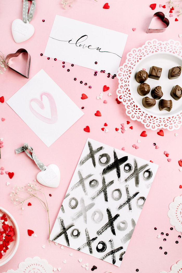 chocolates cards lots of small candy hearts scattered around pink surface valentine's day origin