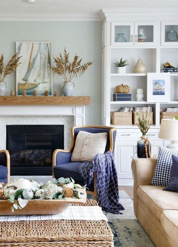 coastal decor blue armchairs beige sofa rattan table placed in front of fireplace white bookshelf on the side