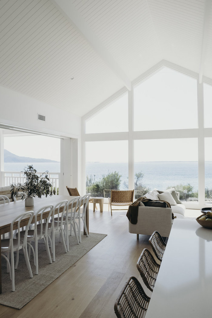 coastal decorating ideas tall cathedral ceiling large windows open plan living room and dining room with long wooden table white chairs