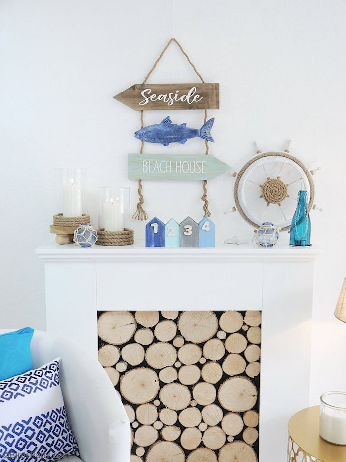 coastal home decor white walls and fireplace filled with wooden logs ocean themed decor on top white armchair in front