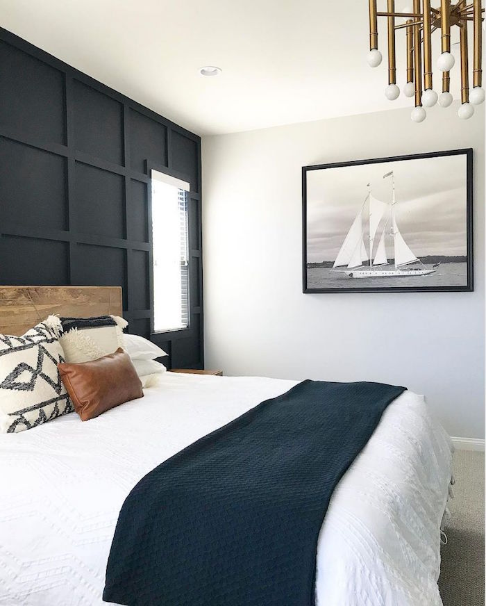 coastal living room bedroom with black accent wall bed with wooden bed frame framed painting of boat on the wall
