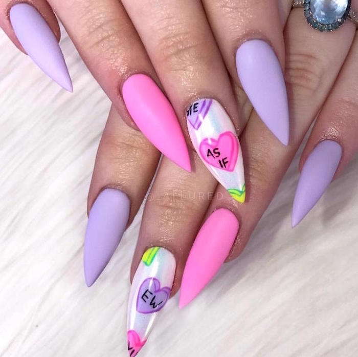 conversation hearts drawn on middle finger valentines day nail art pink and purple matte nail polish on long stiletto nails