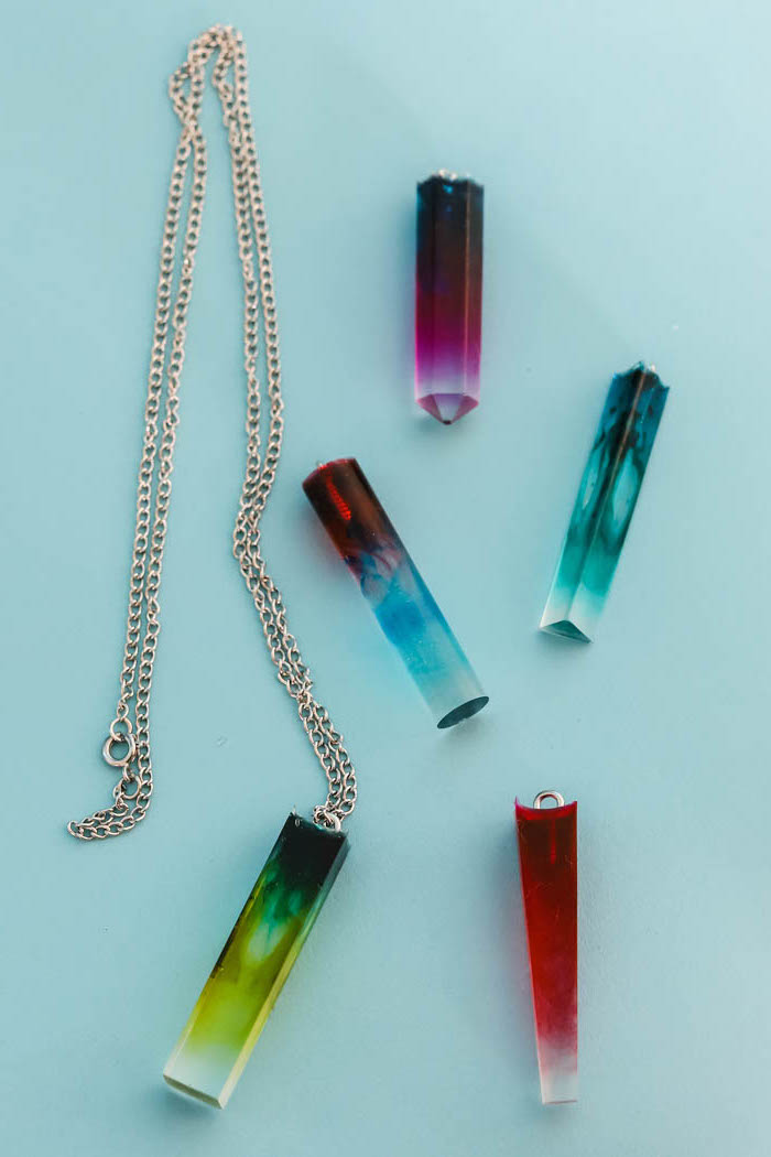crystal like necklace pendants in different colors how to make resin jewelry blue pink red green placed on blue surface