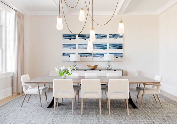 dining room with long wooden table white chairs around it small beach house framed art on white wall