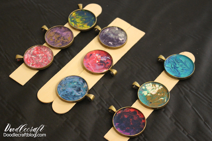 epoxy jewelry nine necklace pendants made with melted crayons in different colors and resin placed on wooden sticks