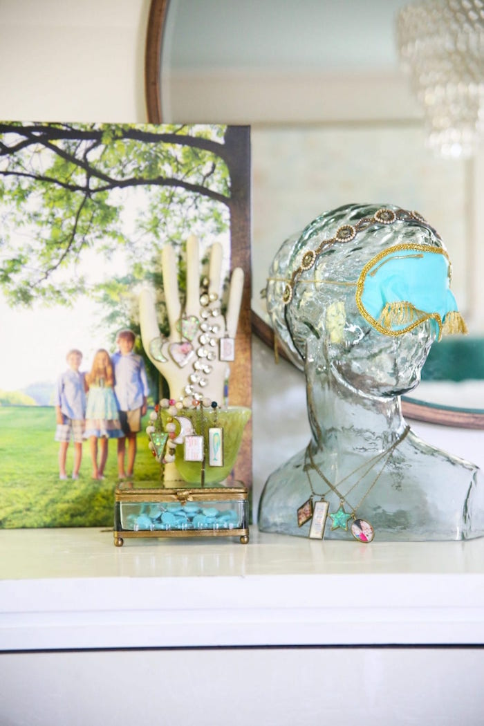 epoxy resin jewelry glass statue next to photo of three children jewelry box with lots of necklaces