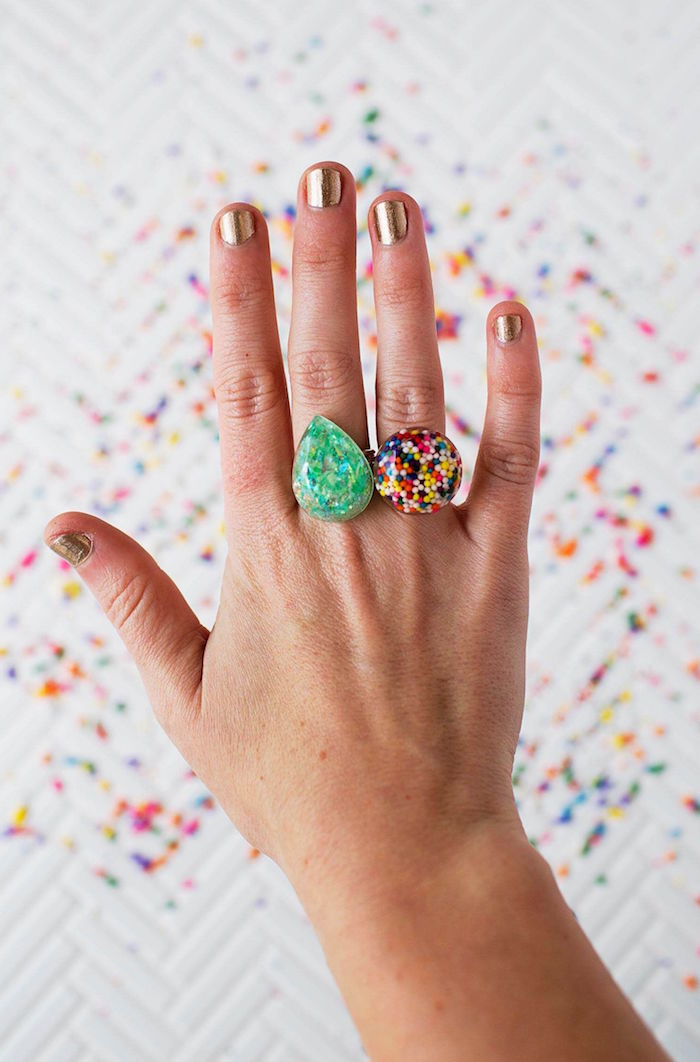 female hand photographed from above with gold glitter nail polish resin jewelry kit two colorful resin rings on index and middle finger