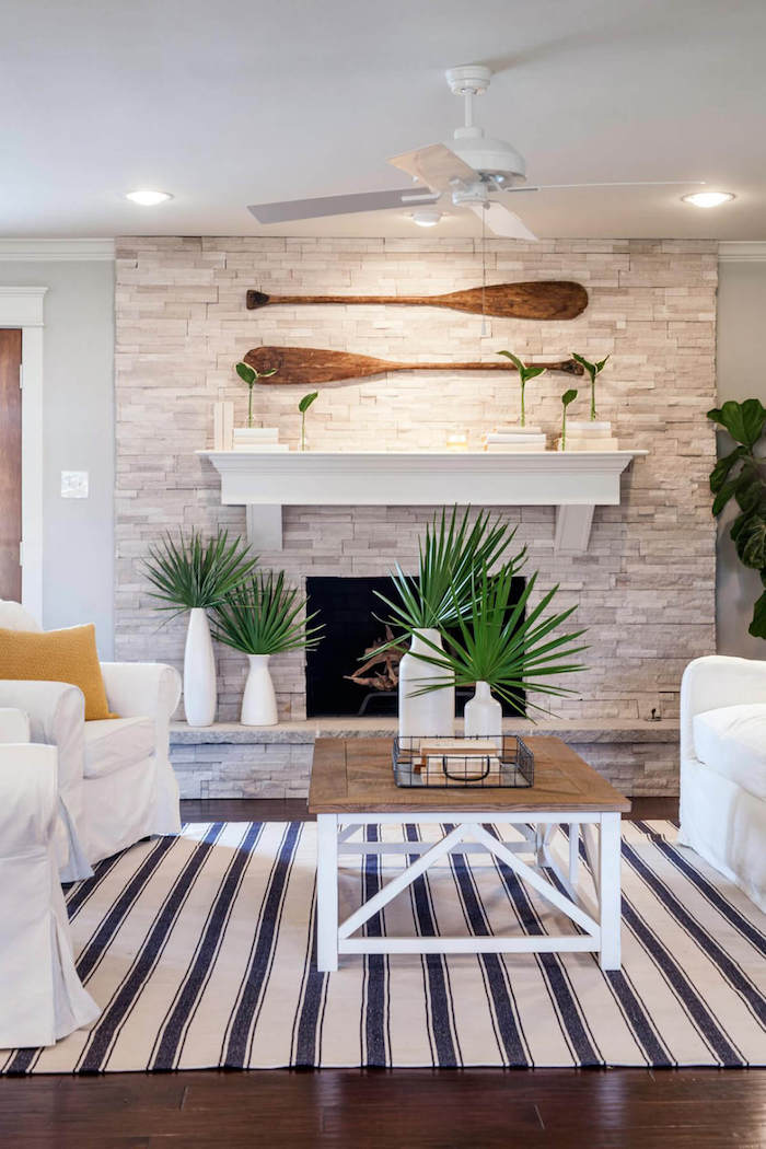 fireplace decorated with stones two paddles on top coastal decor white armchairs and sofa in front of it with wooden coffee table
