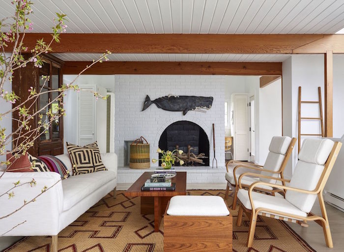 fireplace on white brick wall beach decor ceiling with exposed wod beams white sofa and armchairs wooden coffee table