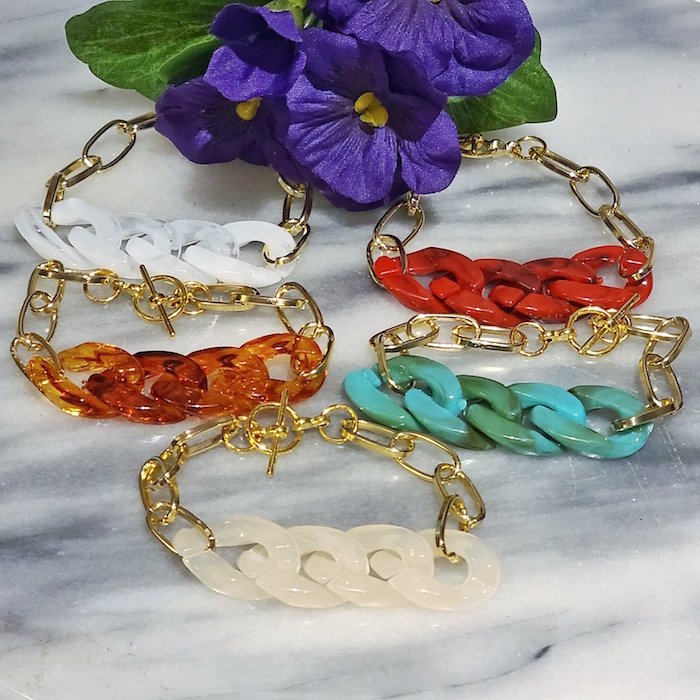 five golden chain bracelets with resin links in different colors resin jewelry red blue white orange resin placed on marble surface