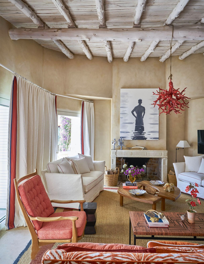 framed art above the fireplace nautical decor two white sofas red armchair exposed wood beams on the ceiling